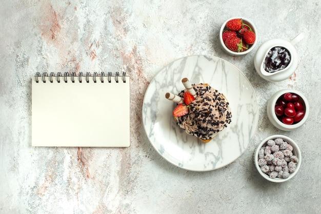 Draufsicht cremiger köstlicher kuchen mit erdbeeren und bonbons auf weißer oberfläche