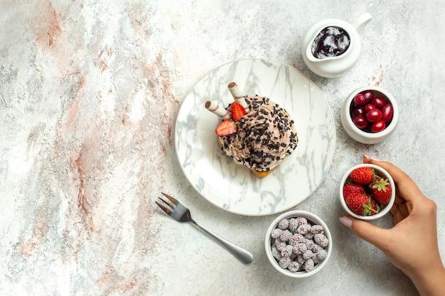 Draufsicht cremiger leckerer kuchen mit erdbeeren und bonbons auf weißer oberfläche geburtstagscremeteekuchen keks süß