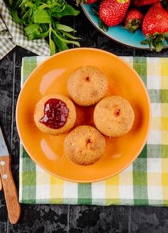 Draufsicht cupcakes mit erdbeermarmelade min und frischer erdbeere auf schwarzem hintergrund