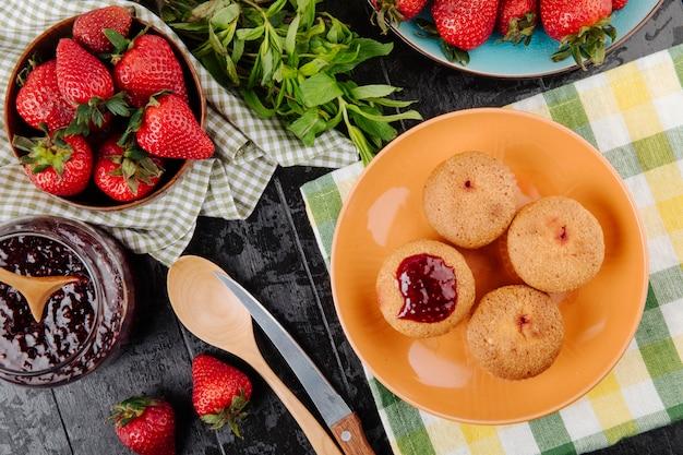 Draufsicht cupcakes mit erdbeermarmelade minze und frischen erdbeeren auf schwarzem hintergrund