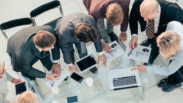 Draufsicht das geschäftsteam arbeitet mit finanzdokumenten im büro