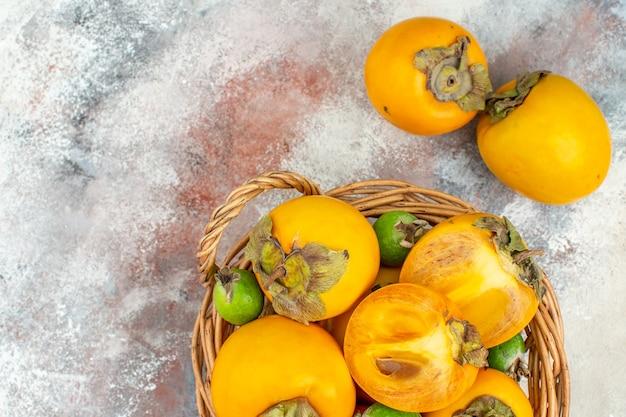 Draufsicht delicios persimmons feykhoas im weidenkorb auf nacktem hintergrund