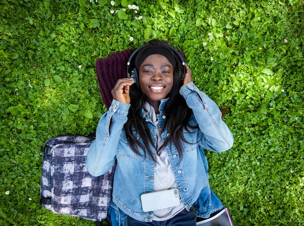 Draufsicht der afrikanischen frau hörend musik mit kopfhörern