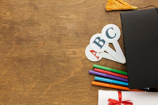 Draufsicht der akademischen kappe mit schulmaterial und diplom