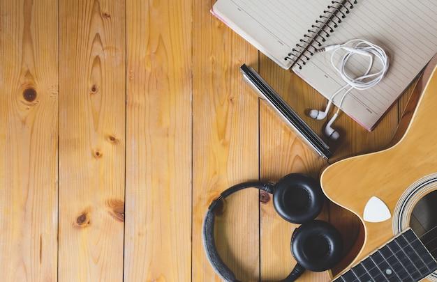 Draufsicht der akustikgitarre mit papier für das zusammensetzen mit kopfhörer und raum für die benennung