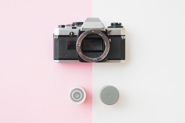 Draufsicht der analaog slr-kamera mit 35-mm-filmkanistern auf rosa
