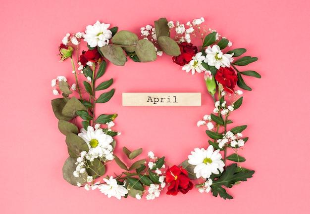 Draufsicht der april-textmitte des bunten blumenkranzes gegen pfirsichoberfläche