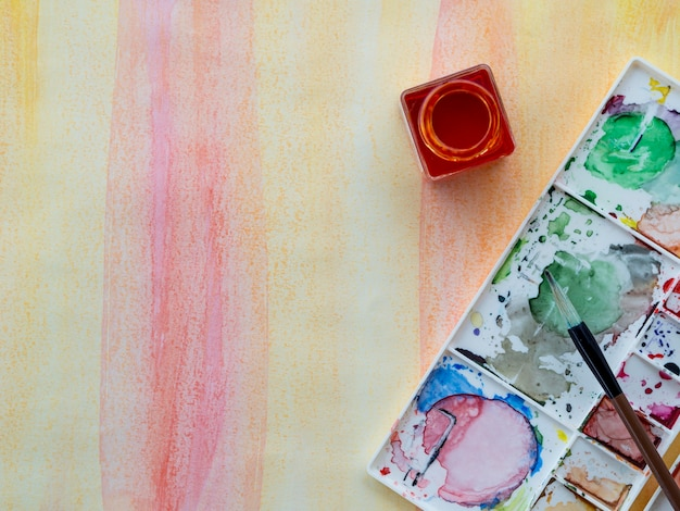 Draufsicht der aquarellfarbe mit pinsel und kopierraum