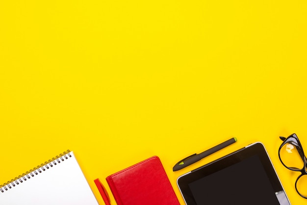 Draufsicht der arbeitsplatztabelle mit dem notizbuch, gläsern, tablette und stift mit copyspace lokalisiert auf gelbem hintergrund