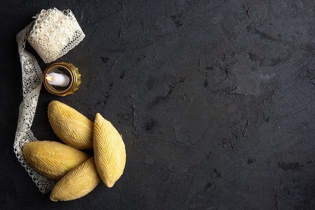 Draufsicht der aserbaidschanischen nationalen dessert-shekerbura mit kerze und spitze auf schwarz