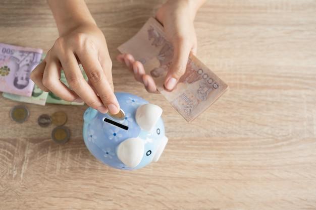 Draufsicht der asiatischen frauenhand legt eine münze in ein sparschwein und hält banknote auf dem tisch