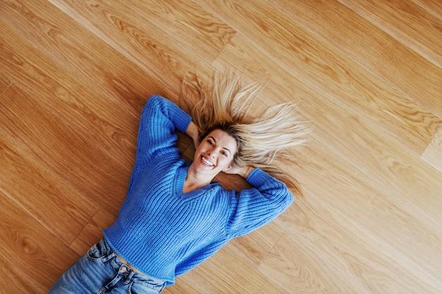 Draufsicht der attraktiven charmanten lächelnden kaukasischen blonden jungen frau im pullover, der auf parkett liegt und schaut
