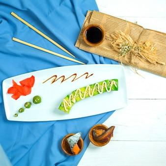 Draufsicht der avocado-sushi-rolle der traditionellen japanischen küche mit aal-tofu-gemüse und avocado-nahaufnahme, serviert mit sojasauce ingwer und wasabi auf blauem und weißem bac