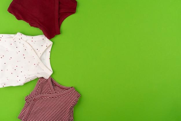 Draufsicht der babykleidung auf grüner oberfläche
