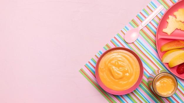 Draufsicht der babynahrung mit äpfeln und löffel