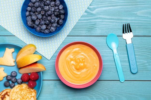 Draufsicht der babynahrung mit schüssel blaubeeren und früchten