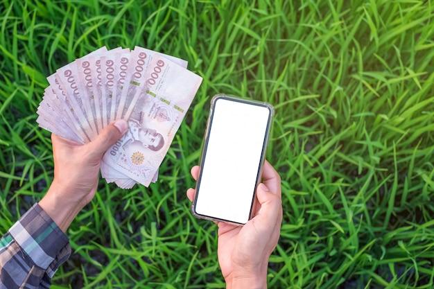 Draufsicht der bauernhand, die thailändische banknoten und den leeren bildschirm des smartphones mit grünem reis am bauernhof hält