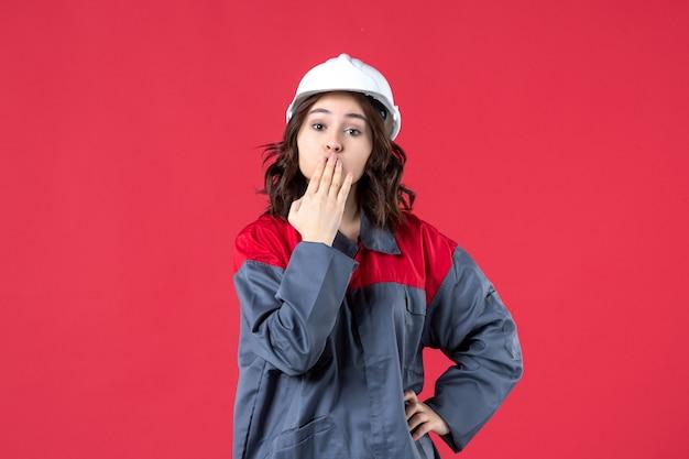 Draufsicht der baumeisterin in uniform mit schutzhelm und kussgeste auf isoliertem rotem hintergrund