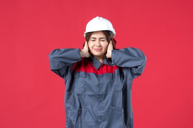Draufsicht der baumeisterin in uniform mit schutzhelm und nervös auf isoliertem rotem hintergrund