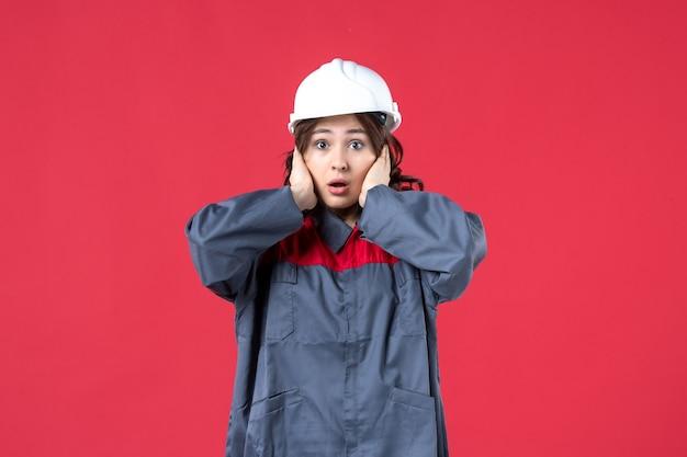 Draufsicht der baumeisterin in uniform mit schutzhelm und schockiert auf isoliertem rotem hintergrund