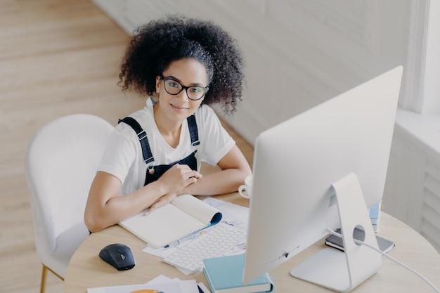Draufsicht der begeisterten gelockten arbeitnehmerin wirft am desktop auf