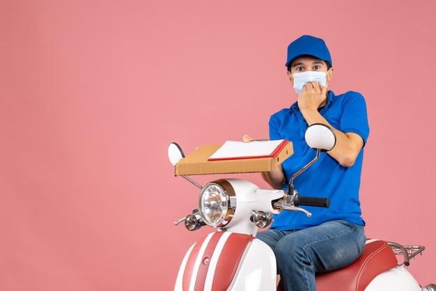 Draufsicht der betroffenen männlichen lieferperson in maske mit hut, die auf einem roller sitzt und bestellungen mit einem dokument auf pfirsichhintergrund liefert
