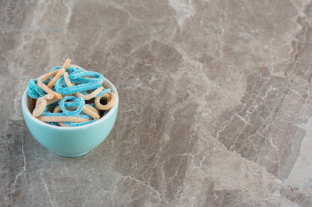 Draufsicht der blauen schüssel voll mit bunten bandbonbons.