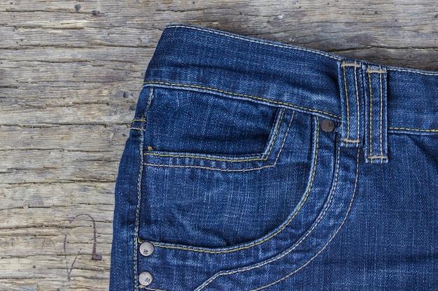 Draufsicht der blue jeans auf altem hölzernem hintergrund.