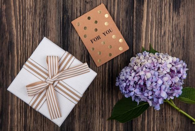 Draufsicht der blume mit geschenkbox und für sie karte auf hölzernem hintergrund