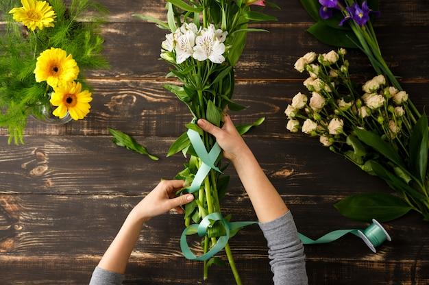 Draufsicht der blumen, florist im prozess der herstellung des blumenstraußes