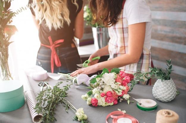 Draufsicht der blumenlieferung. floristen, die ordnung schaffen, rosenblumenstrauß im blumenladen machen. zwei floristinnen machen blumensträuße. eine frau sammelt rosen für ein paar, ein anderes mädchen arbeitet auch.