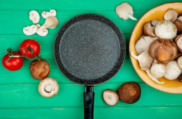 Draufsicht der bratpfanne und der frischen pilze mit tomaten, die auf grün angeordnet sind