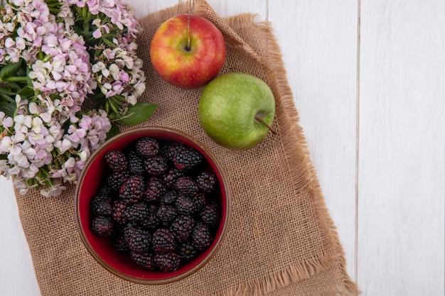 Draufsicht der brombeere in einer schüssel mit äpfeln auf einer beigen serviette mit blumen