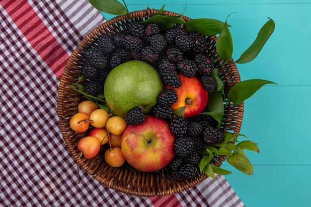 Draufsicht der brombeere mit äpfeln und weißen kirschen in einem korb mit einem roten karierten handtuch auf einer türkisfarbenen oberfläche
