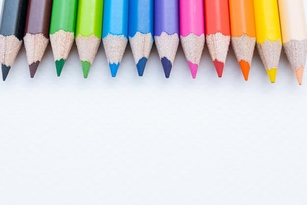 Draufsicht der bunten buntstifte oder des farbstifts, die im bereich auf weißem papier eingestellt werden