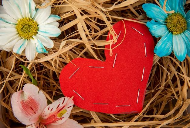 Draufsicht der bunten gänseblümchenblumen und der rosa alstroemeria mit einem herzen, das vom roten farbpapier auf dem stroh-tisch gemacht wird
