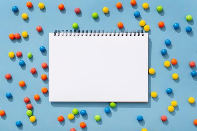 Draufsicht der bunten gummibärchen mit notizbuch