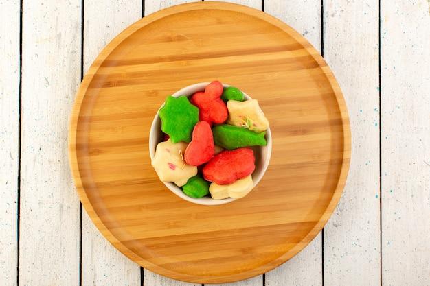 Draufsicht der bunten köstlichen kekse verschieden geformter mehrfarbiger innenplatte auf dem hölzernen schreibtisch