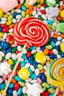Draufsicht der bunten lutscher auf bonbons im mehrfarbigen glasurhintergrund