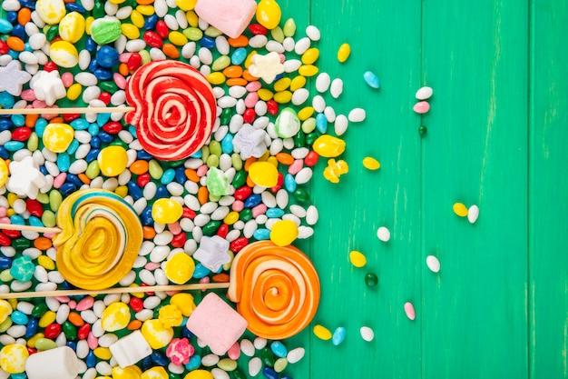 Draufsicht der bunten lutscher und der bonbons in der mehrfarbigen glasur verstreut auf grünem hintergrund mit kopienraum