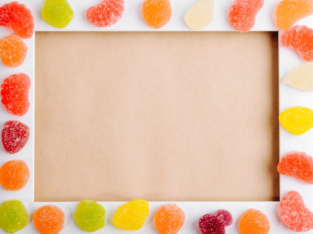 Draufsicht der bunten marmeladenbonbons angeordnet auf einem leeren bilderrahmen