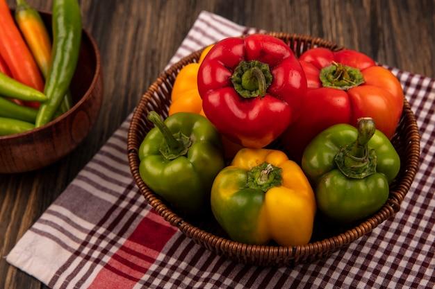 Draufsicht der bunten paprika auf einem eimer auf einem karierten tuch mit lang geformten grünen paprika auf einer schüssel auf einer holzwand