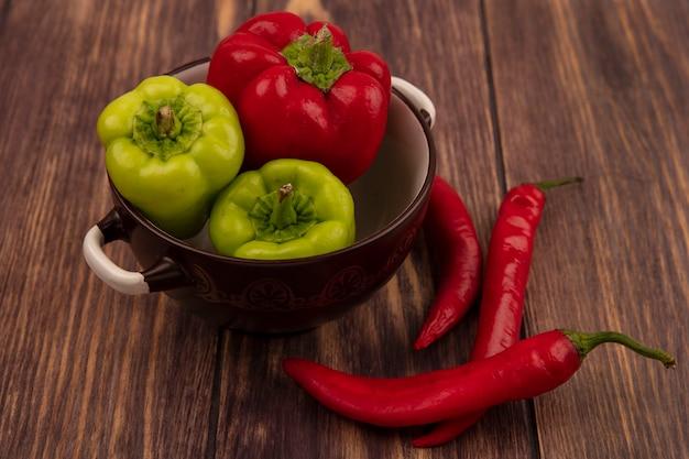 Draufsicht der bunten paprika auf einer schüssel mit chilischoten lokalisiert auf einer holzoberfläche