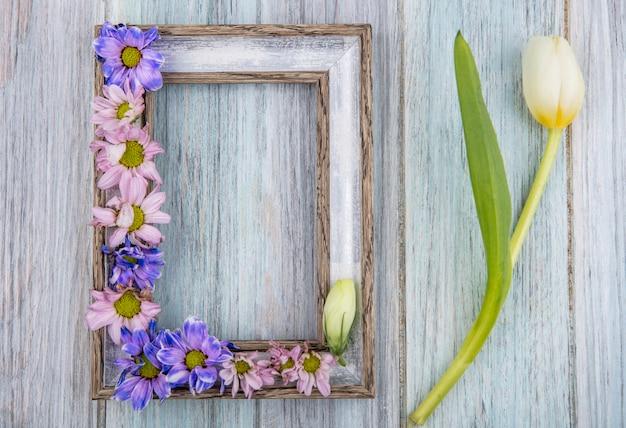 Draufsicht der bunten reizenden gänseblümchenblumen mit weißer tulpe auf einem grauen hölzernen hintergrund mit kopienraum