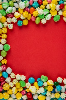 Draufsicht der bunten süßen zuckersüßigkeiten auf rotem hintergrund mit kopienraum