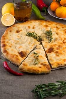Draufsicht der calzone-pizza oder der hühnerpilztorte mit pfeffer, zitrone, rosmarin und tee auf leinengewebehintergrund