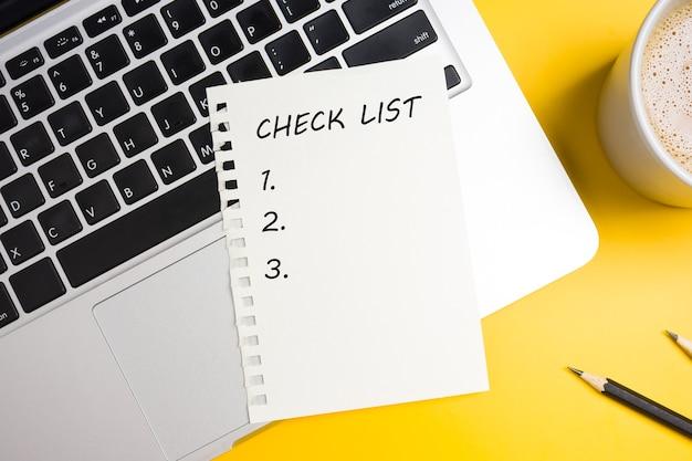 Draufsicht der checkliste, eine tasse kaffee und laptop auf gelbem tisch.