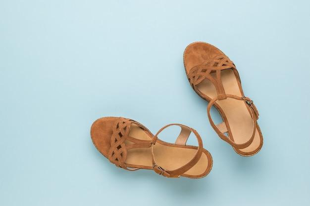 Draufsicht der damen wildleder sandalen auf blauem grund. sommerschuhe für frauen. flach liegen.