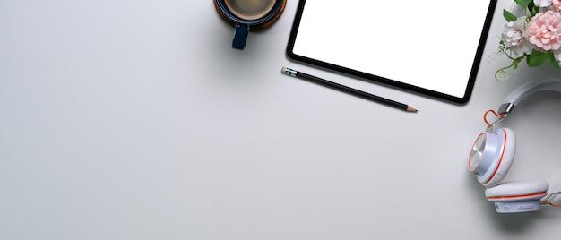 Draufsicht der digitalen tablette mit leerem bildschirm, kaffeetasse, kopfhörer und kopienraum auf weißem hintergrund.