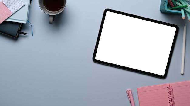 Draufsicht der digitalen tablette mit leerem bildschirm, notebook, kaffeetasse und pflanze auf grauem tisch am kreativen designerarbeitsplatz.